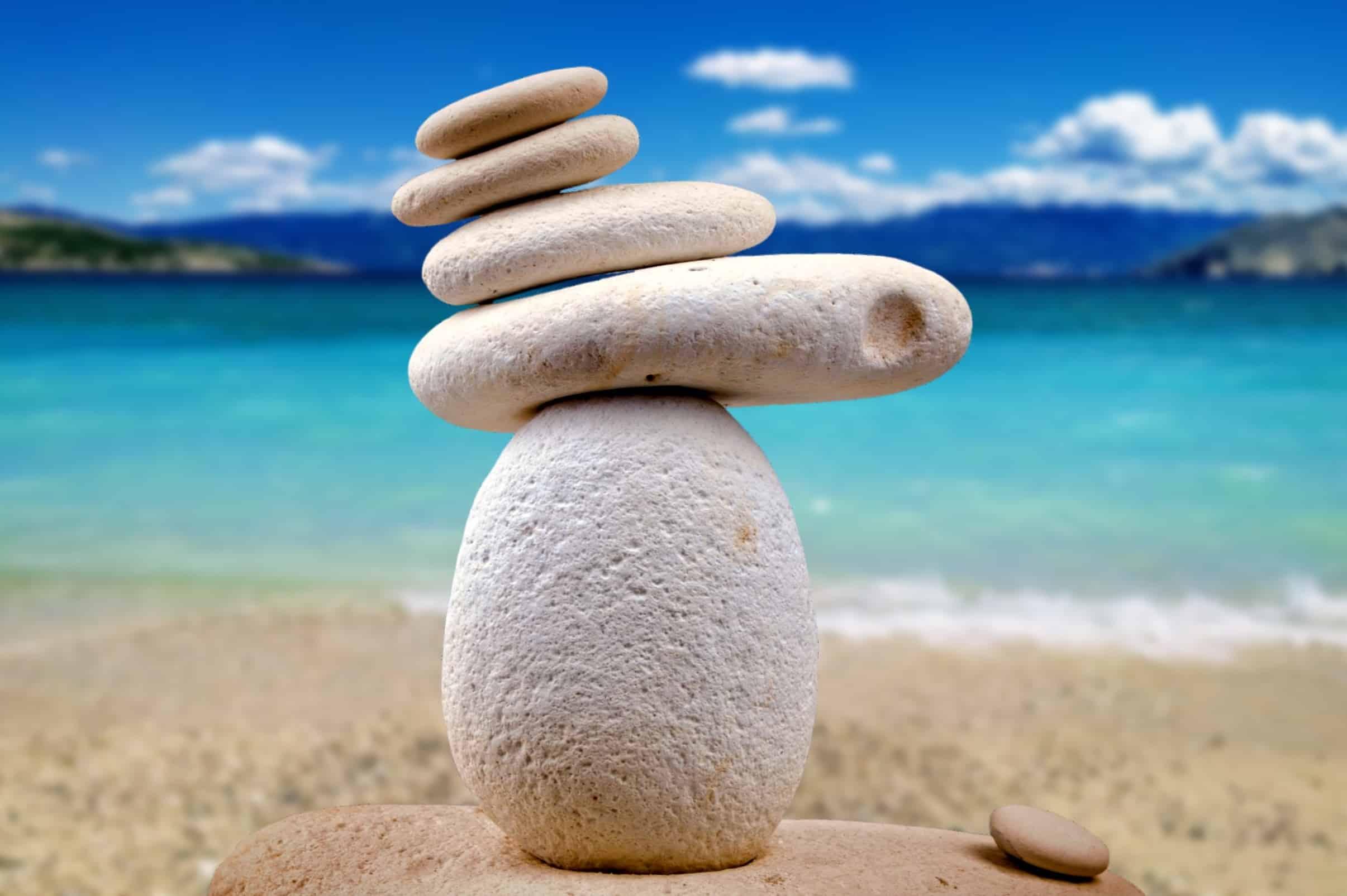 stapel stenen aan het water, overhellend naar links